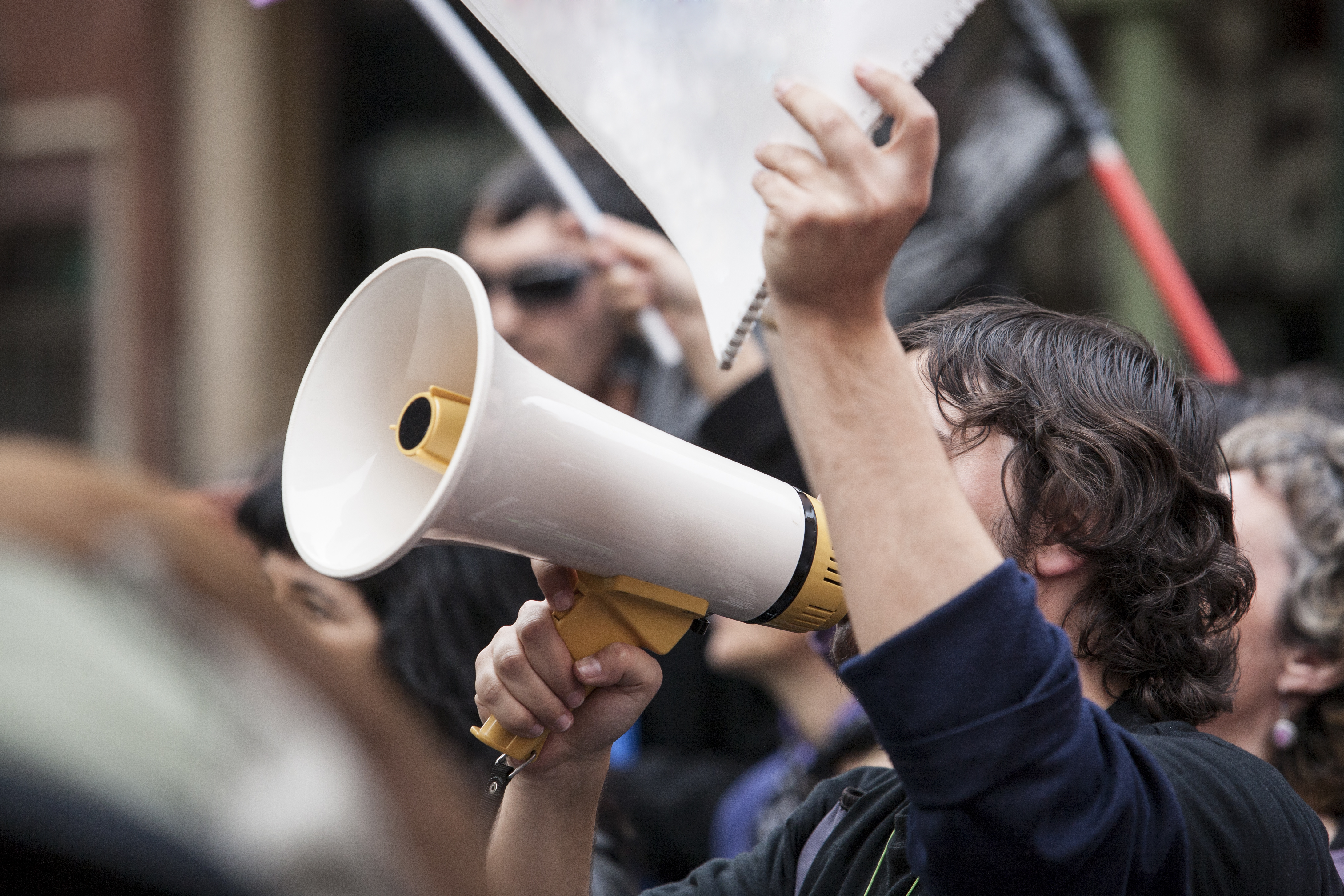 Person speaking into a megaphone at a rally.